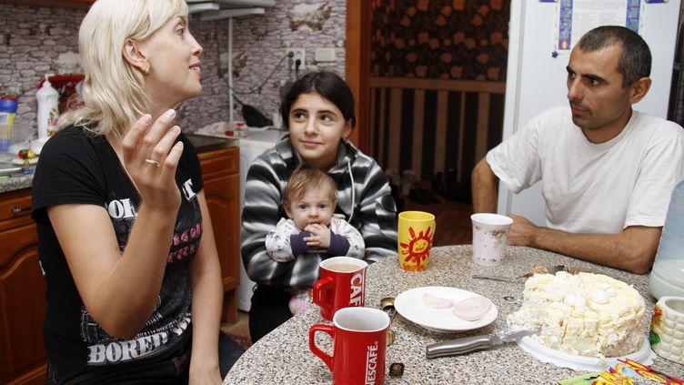 Ioulia Beliaïeva, sa fille Irina et le père biologique de cette dernière, Naimat, à Kopeisk (Russie), en septembre 2011.  (KOMSOMOLSKAYA PRAVDA / VALERY ZVONAREV / AFP)