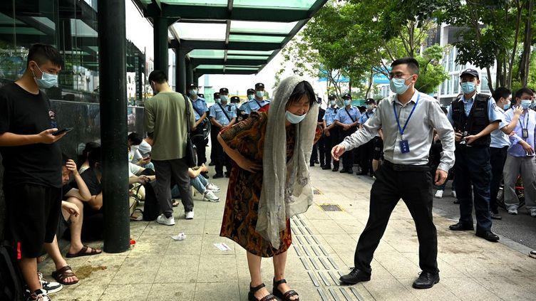 Des manifestants devant le siège d'Evergrande à Shenzhen, dans le sud-est de la Chine, le 15 septembre 2021. Le géant chinois de l'immobilier risque de faire faillite. Sa dette s'élève à 260 milliards d'euros.  (NOEL CELIS / AFP)