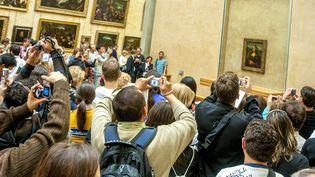 """Des visiteurs du Louvre tentent d'obtenir une photographie de """"La Joconde"""" de Léonard de Vinci, le 17 septembre 2016 à Paris. (BERNARD JAUBERT / ONLY FRANCE / AFP)"""