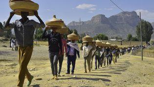 Des Ethiopiens portent des corbeilles d'aliments traditionnels tissées à la main pour se rendre cérémonieusement à une réunion de réconciliation dans le district d'Irob, dans le nord de l'Ethiopie, près de la frontière avec l'Erythrée, le 23 octobre 2019. (MICHAEL TEWELDE / AFP)