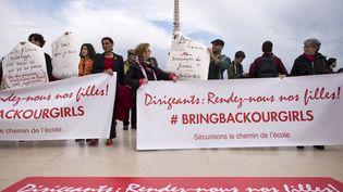 """Des manifestants brandissent des pancartes """"Bring back our girls"""", en soutien aux lycéennes enlevées au Nigeria, à Paris, le 13 mai 2014. (LIONEL BONAVENTURE / AFP)"""