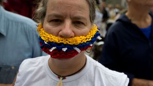 Une femme se couvre la bouche faite auxcouleurs du drapeau du Venezuela lors d'une manifestation dejournalistes et demilitants des droits de l'homme à Caracas, le 3 mai 2016. (FERNANDO LLANO / AP / SIPA)