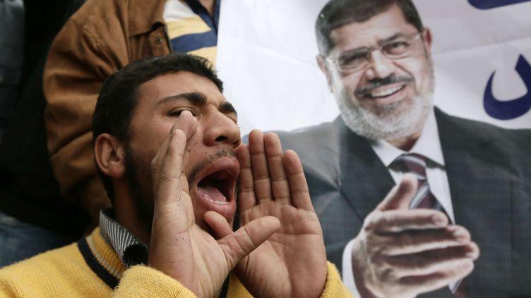 Un supporter du président égyptien Mohamed Morsi (sur l'affiche), manifeste, le 5 décembre, au Caire. (HASSAN AMAR / SIPA)
