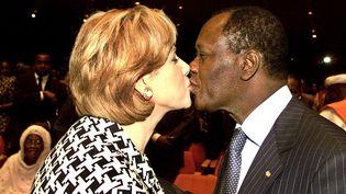 Alassane et Dominique Ouattara échangent un baiser le 1er décembre 2001. Il vient de prononcer un discours dans le cadre d'un forum de réconciliation nationale en Côte d'Ivoire, censé panser les plaies du passé.   (GEORGES GOBET / AFP)