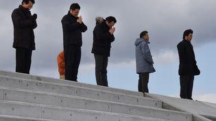 Des Japonais prient, vendredi 11 mars 2016, sur les côtes de Sendai (Japon), en hommage aux victimes du séisme, du tsunami et de la catastrophe nucléaire de Fukushima, survenus cinq ans plus tôt. (TORU YAMANAKA / AFP)