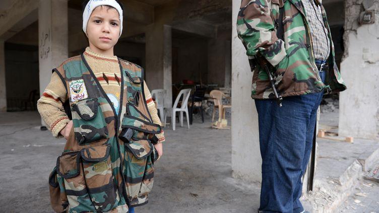 Un enfant portant une veste militaire à un chekpoint de l'Armée syrienne libre au nord d'Alep (Syrie), le 26 octobre 2012. (PHILIPPE DESMAZES / AFP)