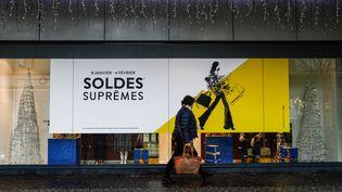 Une piétonne passe devant un panneau publicitaire dans les rues de Caen, le 8 janvier 2020. (SAMEER AL-DOUMY / AFP)