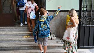 Un élève fait signe à ses proches en arrivant dans son école à Rome pour la rentrée, le 14 septembre 2020. (VINCENZO PINTO / AFP)