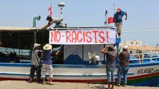Des pêcheurs tunisiens accrochent une banderole antiraciste dans le port deZarzis, dans le sud-est de la Tunisie, le 6 août 2017. (FATHI NASRI / AFP)