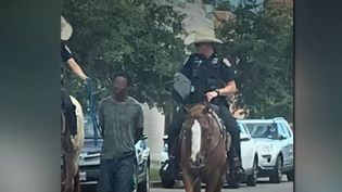 Un homme, tenu par une corde et escorté par des policiers au Texas (États-Unis) (FRANCE 2)
