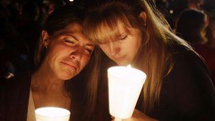 Deux jeunes filles se recueillent après la tuerie de Roseburg (Oregon), le 1er octobre 2015. (RICH PEDRONCELLI / AP / SIPA)