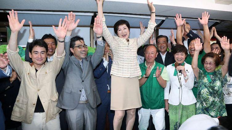 Juchée sur une table, savourant sa victoire, Mme Koike sait qu'elle devra gérer une économie de la taille de celle de l'Indonésie et préparer l'immense agglomération de 13,6 millions d'habitants à un possible tremblement de terre majeur, une crainte omniprésente au Japon depuis le séisme et le tsunami de mars 2011. Mais cette ancienne journaliste, proche des ultranationalistes, n'est pas une nouvelle venue en politique. Elle a été successivement ministre de l'Environnement et de la Défense, et parle couramment l'anglais et l'arabe. Une rareté dans l'archipel. (JIJI PRESS / AFP)