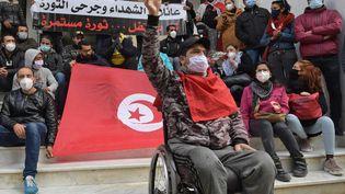 Un jeune Tunisien blessé pendant la révolution crie des slogans anti-gouvernementaux lors d'un sit-in, le 14 janvier 2021, dans la capitale Tunis. (FETHI BELAID / AFP)