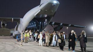 Des personnes évacuées de Kaboul (Afghanistan), débarquent à la base militaire française Al Dhafra (Emirats Arabes Unis), le 26 août 2021. (ETAT MAJOR DES ARMEES / AFP)