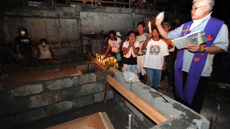 Un prêtre bénit les cercueils de victimes des inondations, au cimetière d'Iligan, le 20 décembre 2011. (TED ALJIBE / AFP)