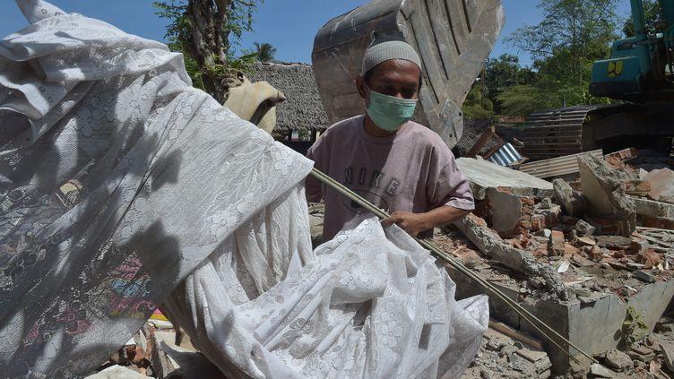 Un homme s'active pour évacuer les décombres après le séisme à Lombok (Indonésie), le 12 août 2018. (ADEK BERRY / AFP)