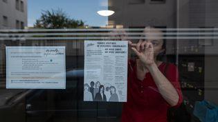 Une femme scotche une feuille de papier avec des informations et numéros d'urgence à destination des femmes victimes de violences conjugales dans le hall d'entrée d'un immeuble à Nantes, le 15 avril 2020. (JEREMIE LUSSEAU / HANS LUCAS / AFP)
