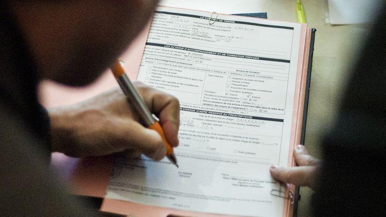 Un jeune homme signe un contrat de travail, à Beauvais (Oise), le 17 mai 2013. (FRED DUFOUR / AFP)