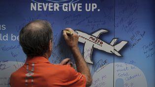 Un homme écrit un message de soutien sur un mur lors d'une manifestation des proches des victimes du crash du MH370 àKuala Lumpur (Malaisie), le 8 mars 2014. (AIMAN ARSHAD / CROWDSPARK / AFP)