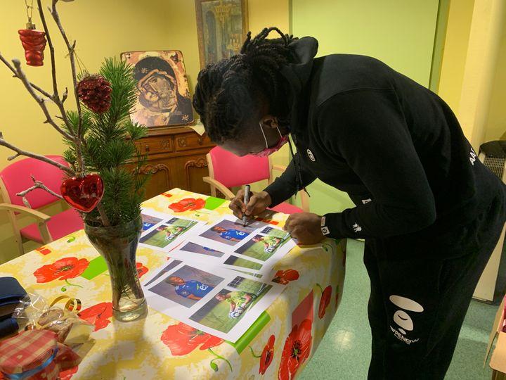 Lebo Mothiba signe des petites cartes, déstinées aux résidents de l'EHPAD, ainsi qu'au personnel.