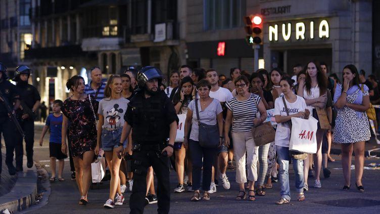 Des policiers évacuent des riverains et des touristes après l'attentat de Barcelone (Espagne), le 17 août 2017. (PAU BARRENA / AFP)
