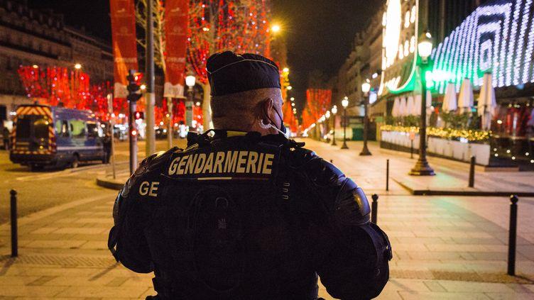 Un policier sur les Champs-Elysées durant la nuit de la Saint-Sylvestre,le 1er janvier 2021, à Paris. (PHILIPPE LABROSSE / HANS LUCAS / AFP)