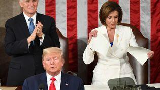 Le vice-président américain Mike Pence (à gauche) debout à côté de la cheffe de file des démocrates à la Chambre des représentants Nancy Pelosi (à droite) qui déchire une copie du discours sur l'état de l'Union de Donald Trump, aux Etats-Unis, le 4 février 2020. (MANDEL NGAN / AFP)