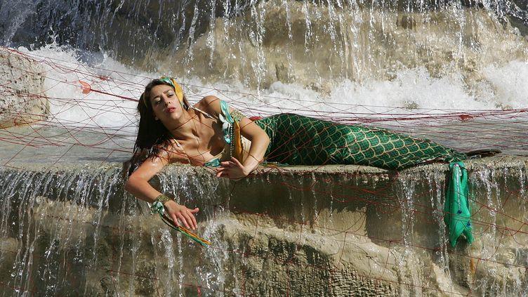 Une activiste de Greenpeace déguisée en sirène manifeste à Rome (Italie), le 13 juillet 2006. (MAX ROSSI / REUTERS)