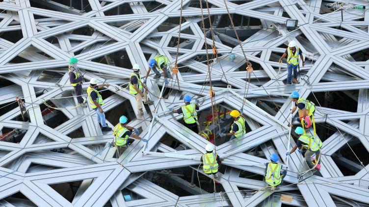 Des ouvriers achèvent dimanche 27 septembre 2015 le dôme monumental du Louvre Abu Dhabi.  (WAM / AFP)