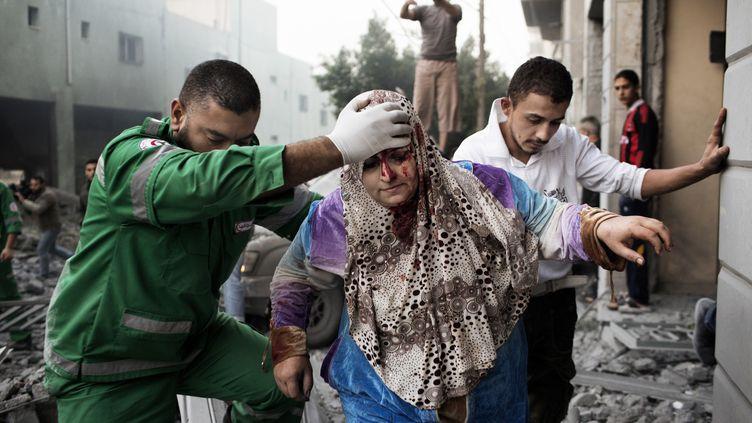 Deux hommes aident une Palestinienne à sortir de son immeuble, endommagé lors d'un raid aérien israélien dans la ville de Gaza, le 19 novembre 2012. (MARCO LONGARI / AFP)