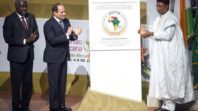 De gauche à droite, le président de la Commission de l'Union africaineMoussa Faki Mahamat, et les présidents égyptien et nigérien, Abdel Fattah al-Sissi et Mahamadou Issoufou. Ils applaudissent au lancement de la phase opérationnelle de la zone de libre-échange africaine le 7 juillet 2019 à Niamey, lors du sommet des chefs d'Etat de l'Union africaine. (ISSOUF SANOGO / AFP)