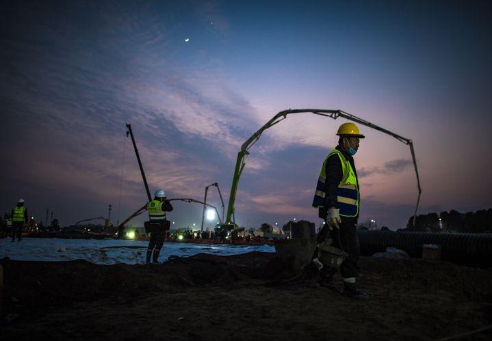 Des ouvriers s'afférant sur le site de chantier de construction de l'hôpital deHuoshenshan, à Wuhan, le 28 janvier 2020. (XIAO YIJIU / XINHUA / AFP)