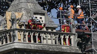 Des pompiers et des techniciens à l'œuvre sur un balcon de la cathédrale Notre-Dame de Paris, vendredi 19 avril 2019. (LIONEL BONAVENTURE / AFP)