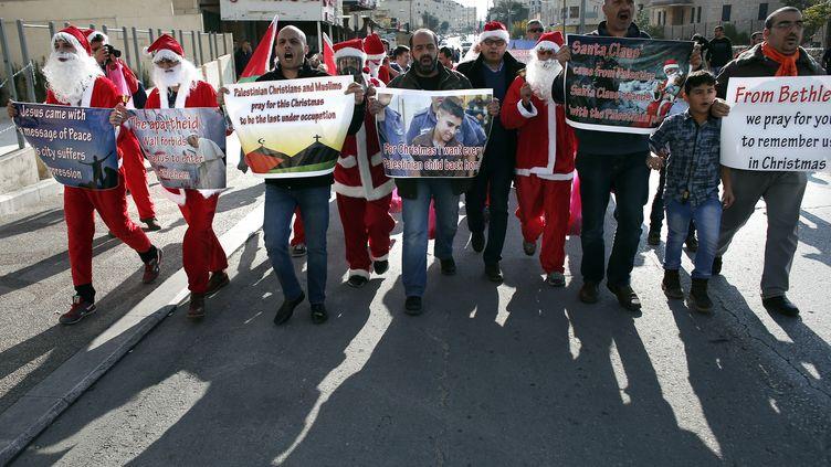 Des Palestiniens, dont certains habillés en Père Noël, manifestent contre le mur de séparation controversée israélienne dans la ville de Bethléem (Cisjordanie), le 18 décembre 2015. (THOMAS COEX / AFP)
