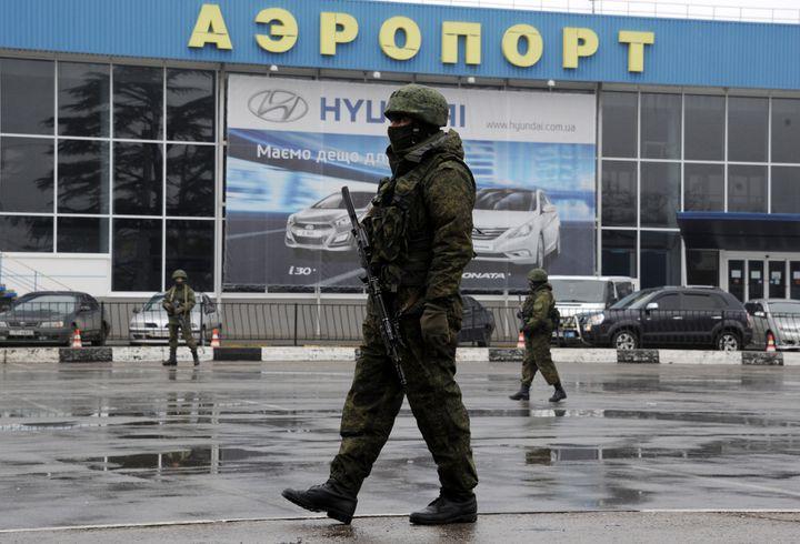 Un homme armé patrouille devant l'aéroportSimferopol, en Crimée. (VIKTOR DRACHEV / AFP)
