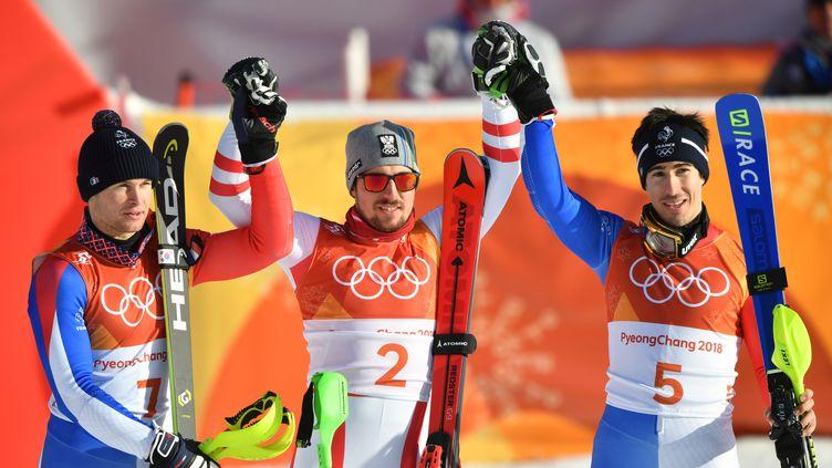 Les skieurs français Alexis Pinturault (à gauche) et Victor Muffat-Jeandet (à droite) entourent l'Autrichien Marcel Hirscher, après leurs médailles d'argent et de bronze dans l'épreuve du combiné des Jeux olympiques de Pyeongchang, le 13 février 2018. (FABRICE COFFRINI / AFP)