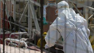 Un médecin pousse un brancard sur lequel est allongé un patient de 16 ans atteint d'Ebola, le 22 décembre 2014, enSierra Leone. (BAZ RATNER / REUTERS)