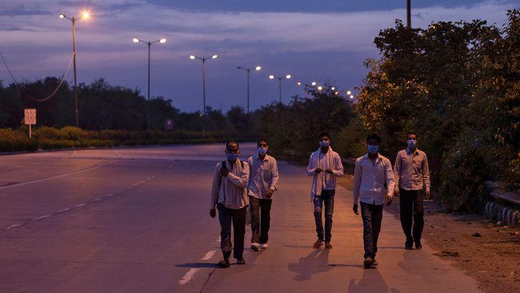 Des travailleurs rentrent chez eux, à proximité de New Delhi, en Inde, où un confinement a été décrété pour trois semaines, le 25 mars 2020. (DANISH SIDDIQUI / REUTERS)