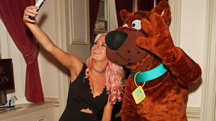 """Londres, 18 août 2016. Chloé Paige fait un selfie avec Scooby-Doo à la présentation presse de """"Scooby-Doo Live ! Musical Mysteries"""" au Paladium. (David M. Benett/Dave Benett/Getty Images)"""