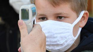 La température d'un enfant masqué contre le coronavirus prise avant son entrée à l'école (photo d'illustration). (DAMIEN MEYER / AFP)