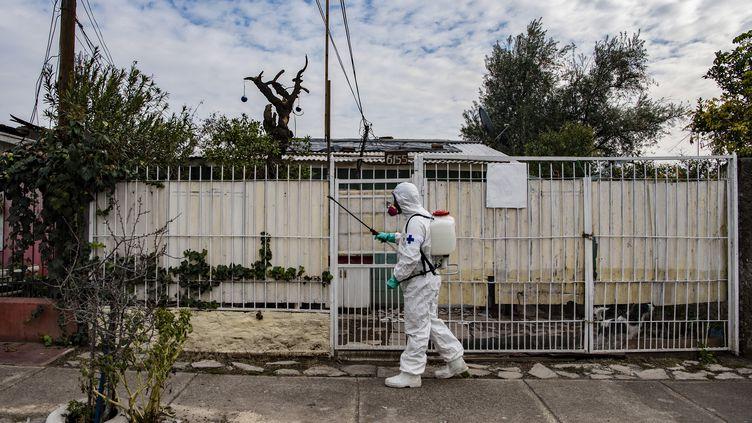 Un homme désinfecte les rues de Santiago, la capitale du Chili, le 7 juillet 2020. (MARTIN BERNETTI / AFP)