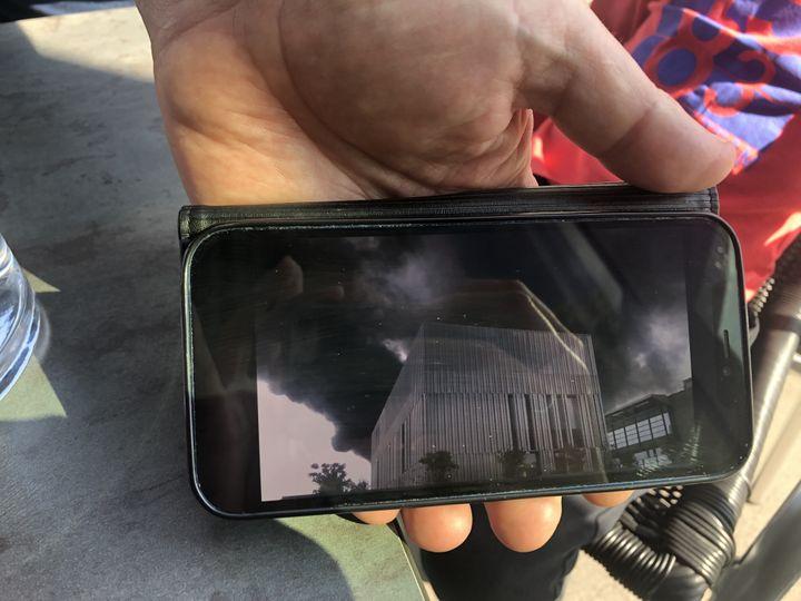 Pierre-Emmanuel Brunet montre sur son écran de téléphone lesfumées noires filmées le jour de l'incendie de Lubrizol de 2019, à Rouen, le 23 septembre 2021. (LOUISA BENCHABANE / FRANCEINFO)