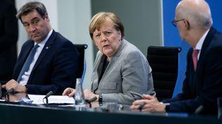 La chancelière allemande, Angela Merkel, tient une conférence de presse sur le coronavirus, entourée du ministre-président de Bavière, Markus Söder, et du premier bourgmestre de Hambourg, PeterTschentscher, le 15 avril 2020 à Berlin. (BERND VON JUTRCZENKA / DPA / AFP)