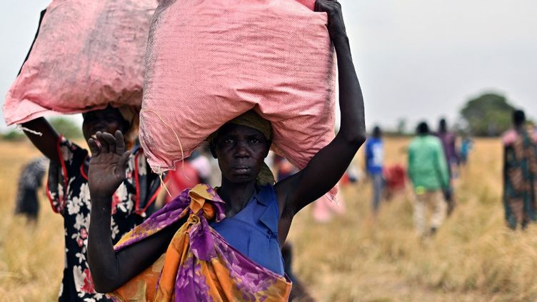 Des villageoises récupèrent des aides duProgrammealimentaire mondial, le 6 février 2020, dans le village d'Ayod (Soudan du Sud). (TONY KARUMBA / AFP)