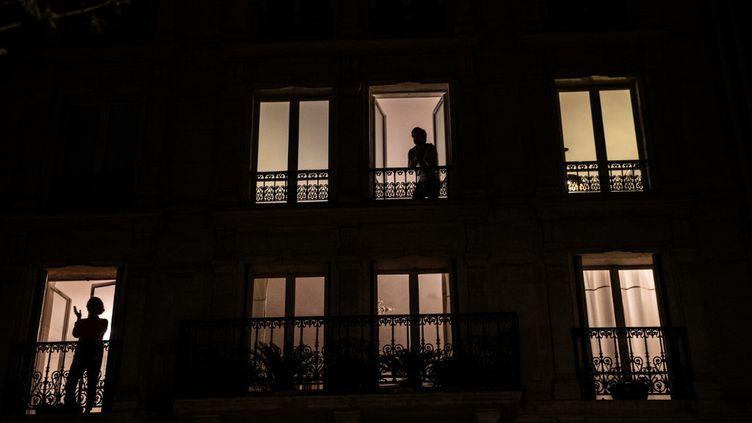 Des personnes à leurs fenêtres, la nuit, pendant le confinement. (MARTIN BUREAU / AFP)