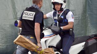 Un policier emporte l'arme avec laquelle un jeune homme a tué trois personnes à Istres (Bouches-du-Rhône), le 25 avril 2013. (GERARD JULIEN / AFP)