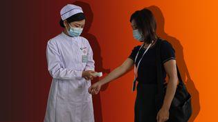 Un contrôle de température à l'entrée d'un hôpital de Wuhan (Chine), le 3 septembre 2020. (Hector RETAMAL / AFP)