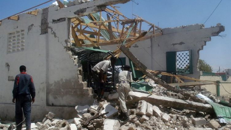 Un policier somalien sur les ruines d'un bâtiment attaqué par l'attentat suicide du 21 février, à Mogadiscio (AFP PHOTO / ABDURASHID ABDULLE ABIKAR)