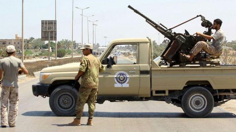 Des forces de sécurité libyennes montent la garde à un poste de contrôle, le 23 août 2018, sur le site d'une attaque dans la ville de Zliten, à 170 km à l'est de la capitale Tripoli. Cette attaque avait tué six soldats du gouvernement Sarraj soutenu par l'ONU. (MAHMUD TURKIA/AFP)