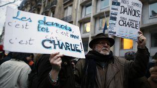 Des participants au rassemblement organisé en hommage aux victimes de la double fusillade de Copenhague, dimanche 15 février devant l'ambassade du Danemark à Paris. (THOMAS SAMSON / AFP)